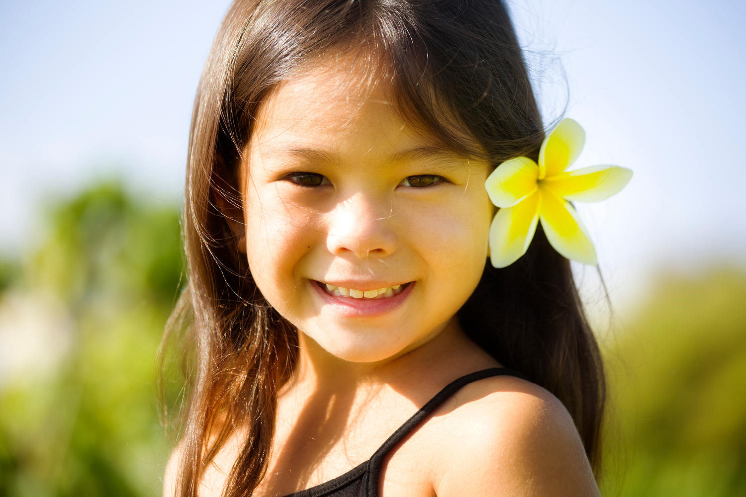 Cute little brunette girl with yellow plumeria blossom in her hair