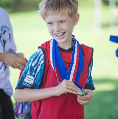 Young special needs youth with ribbon award