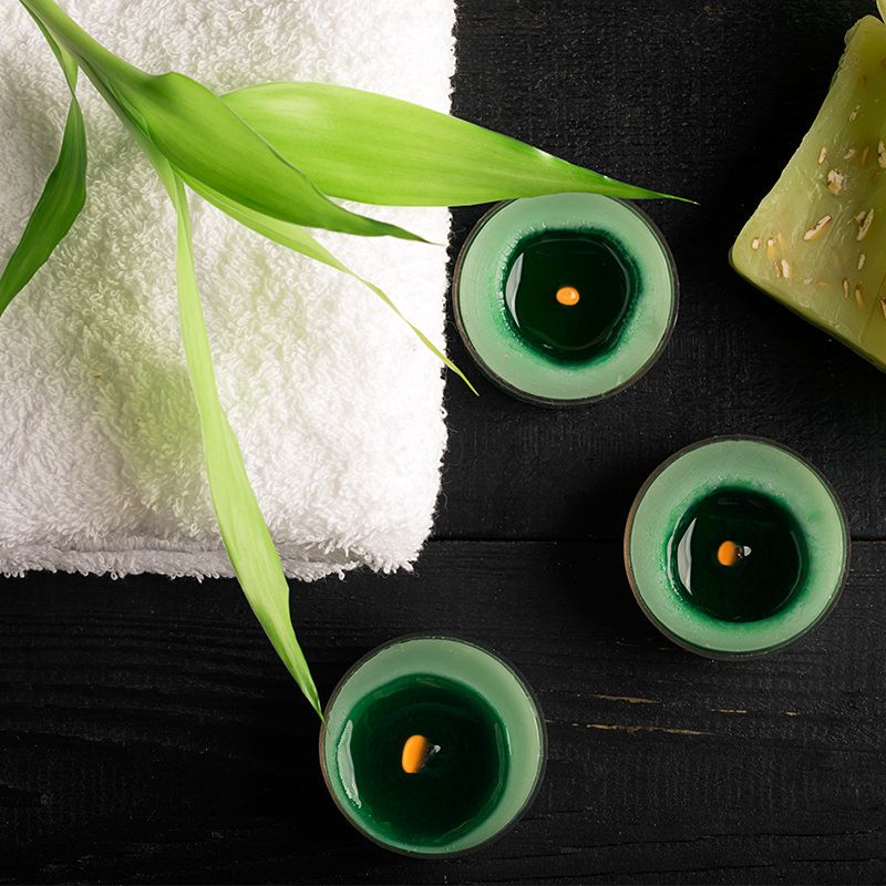 Three lit green candles, a green plant, and a white towel