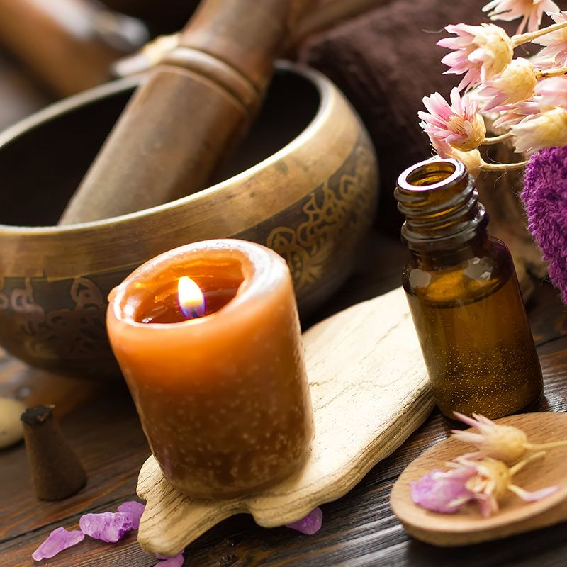 Mortar and pestle, lit candle and dried flowers