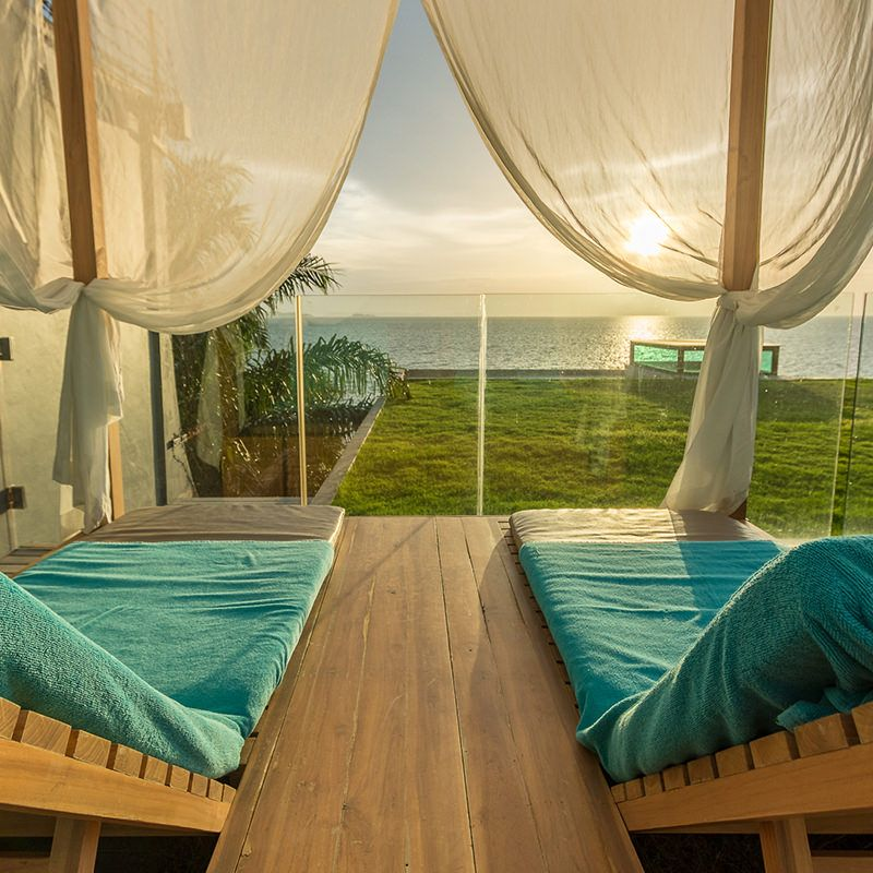 Two chaise lounge chairs looking out a draped patio over grass to the ocean at sunset