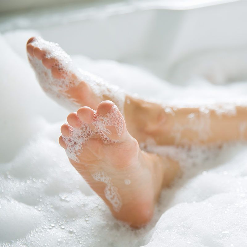 Soapy feet propped up on edge of tub